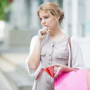 Woman looking worried holding shopping bag
